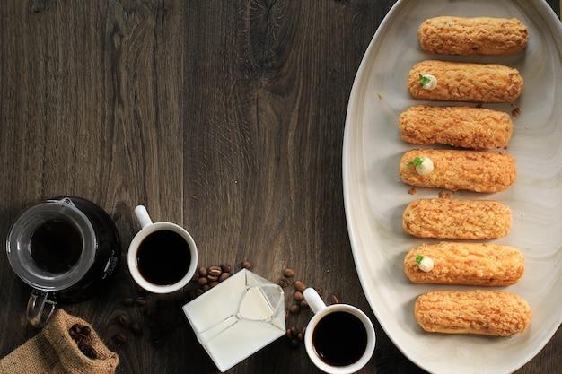 Tiger eclair/craquelin eclair, köstliches französisches brandteig-dessert über schwarzem drahtgestell, frisch gebacken, bereit zum befüllen mit sahne. platz für text/werbung kopieren