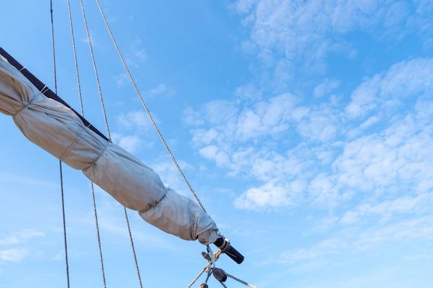 Tigging und maste eines alten segelschiffs gegen den blauen himmel mit wolken. kopieren sie platz.