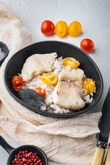 Tilapia-fisch mit basmatireis und kirschtomaten, in schüssel, auf weißem tisch