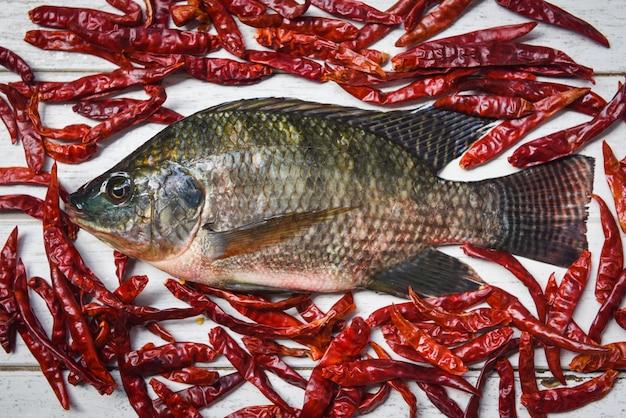 Tilapiafischfrischwasser und getrocknete paprikas für das kochen des lebensmittels im asiatischen restaurant frischer roher tilapia auf hölzernem