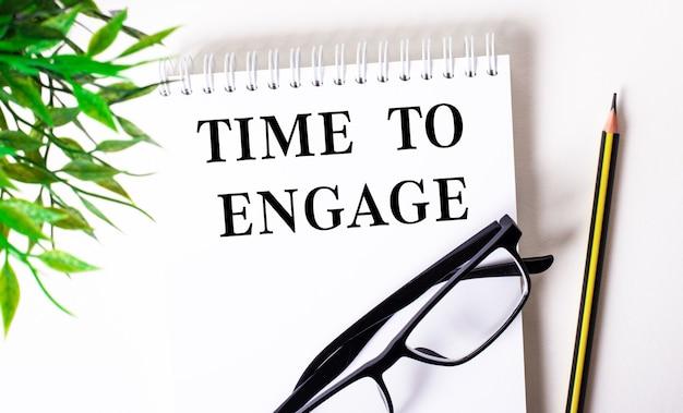Time to engage steht in einem weißen notizbuch neben einem bleistift, einer schwarz gerahmten brille und einer grünen pflanze