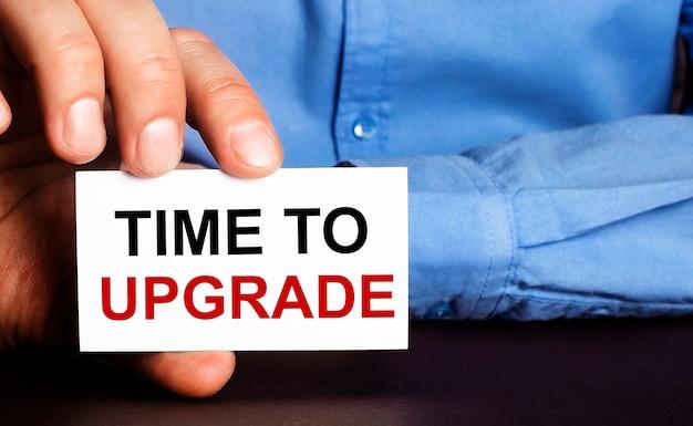 Time to upgrade steht auf einer weißen visitenkarte in der hand eines mannes