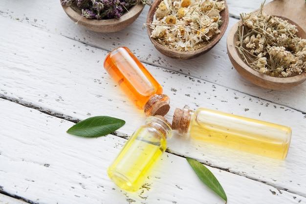 Tinkturen von kräutern in glasflaschen und trockenen kräutern auf einem holztisch. konzept der traditionellen medizin und kräuterbehandlung.