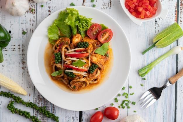 Tintenfisch gebraten mit curry-paste in weißen teller, mit gemüse und beilagen auf einem weißen holzboden.