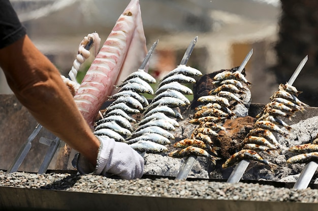 Tintenfisch in der hand des mannes fisch spucken auf feuerstrandhintergrund