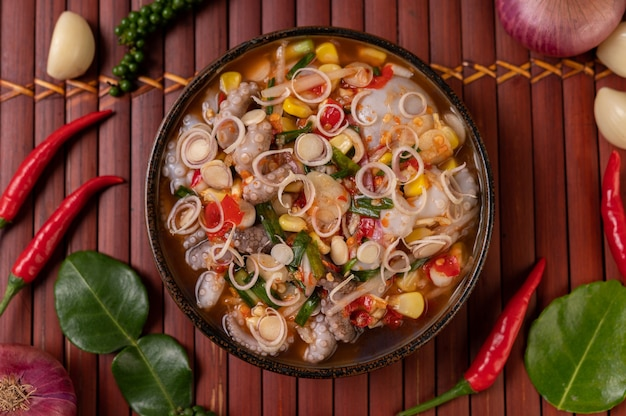 Tintenfischsalat mit koriander, gehackten frühlingszwiebeln, knoblauch und mais auf dem teller