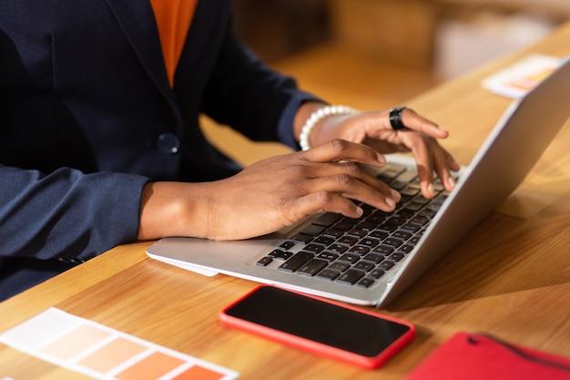 Tippen auf dem laptop. nahaufnahme eines beschäftigten innenarchitekten, der eine nachricht für den kunden auf dem laptop schreibt