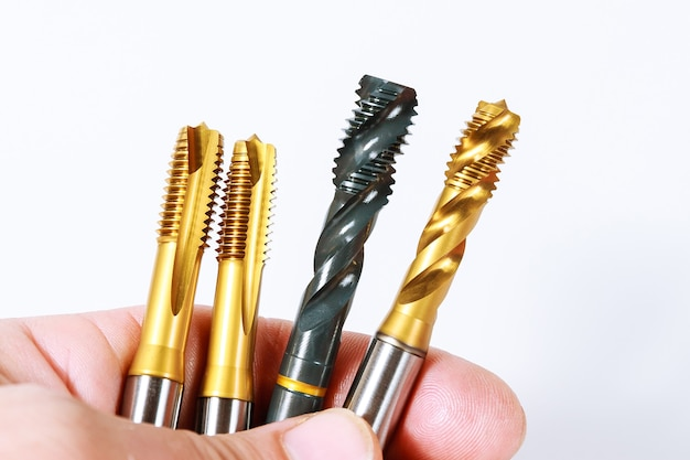 Tippen sie zum einfädeln von metall auf weiße oberfläche. werkzeug für die metallbearbeitung.