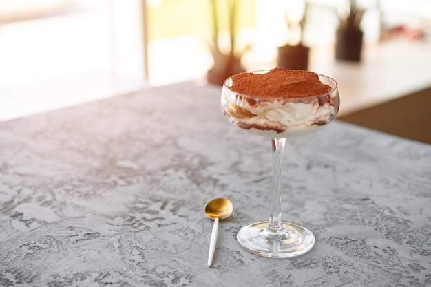 Tiramisu-dessert in einem glas auf grauer oberfläche
