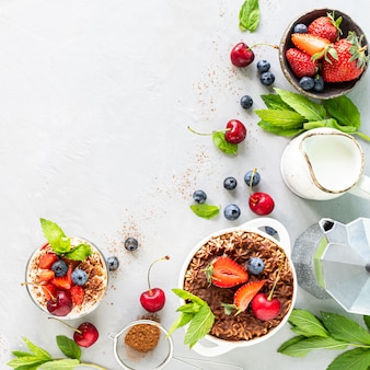 Tiramisu italienisches dessert und zutaten zum kochen. kaffee, kakao, erdbeeren, minze auf weißem hintergrund. kopieren sie die draufsicht auf den speicherplatz