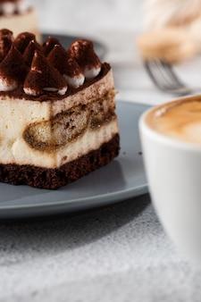 Tiramisu - klassisches dessert mit mascarpone und kaffee. köstlicher tiramisu-kuchen auf einem darck-teller auf einem hellen marmorhintergrund. vertikales foto.