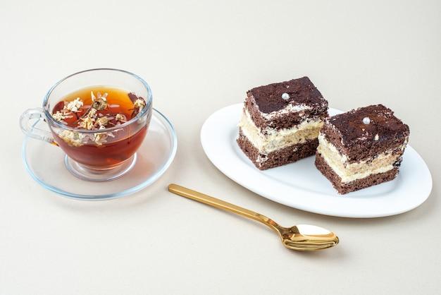 Tiramisu-kuchen und eine tasse tee auf weißer oberfläche mit löffel.