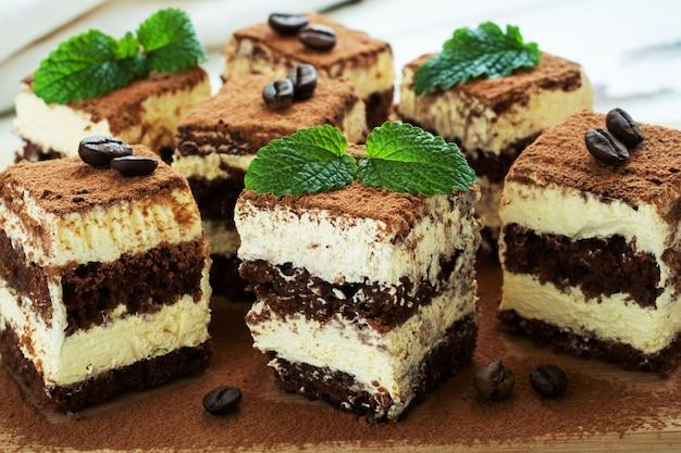 Tiramisu-kuchenstücke mit zarter sahne, kaffeebohnen und minzblättern.