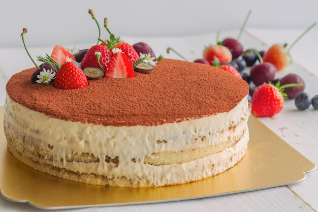 Tiramisukuchen mit kakaopulver bestreuen und mit frischen früchten dekorieren. italienischer klassiker