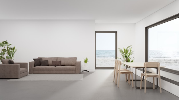 Tisch auf betonboden des großen esszimmers in der nähe des wohnbereichs und des sofas im modernen strandhaus oder luxushotel.