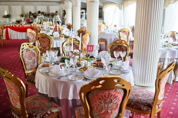Tisch beim hochzeitsbankett im restaurant, klassischer stil mit weißen tischdecken und servietten, vasen mit blumen.