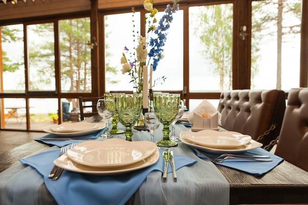 Tisch für die hochzeit mit blumen, dekorationen und kerzen