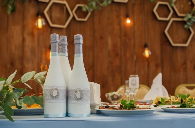 Tisch im restaurant mit tellern, gläsern und weißen flaschen mit champagner serviert. banketttisch auf der geburtstags- oder hochzeitsfeier. drei dekorierte champagnerflaschen auf dem festlichen tisch hautnah.