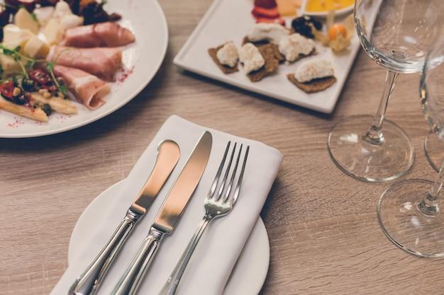 Tisch im restaurant mit vorspeise, besteck und gläsern