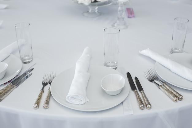 Tisch im restaurant serviert. sauberes weißes tellerlayout auf einer weißen tischdecke.