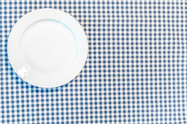 Tisch mit blauem picknicktuch und teller