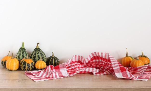 Tisch mit dekorativen kürbissen und einem karierten handtuch leerer platz für ihr objekt ein herbstmodell für halloween oder thanksgiving