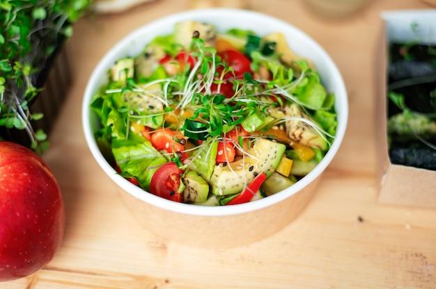 Tisch mit gesundem salat. nahaufnahme, anderes essen in der nähe auf dem holztisch