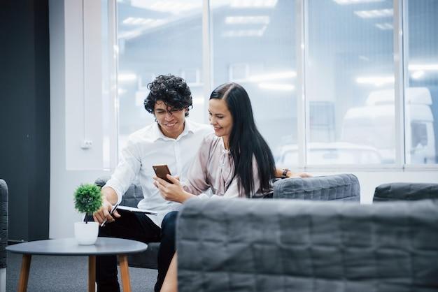 Tisch mit grünpflanze drauf. mitarbeiter im büro, die etwas lustiges material auf dem smartphone lächeln und aufpassen