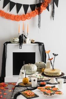 Tisch mit halloween-party-leckereien und dekorationen