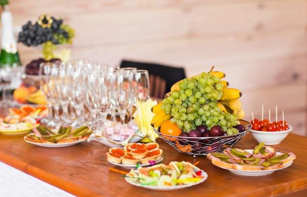 Tisch mit kalten snacks und geschirr auf standup-party