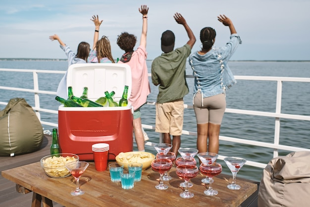 Tisch mit kühlbox voller bier, snacks und cocktailgetränken auf dem tisch, junge leute winken und schauen auf wasser im hintergrund