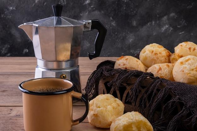 Tisch mit leckeren käsebroten, einer kaffeetasse und einer traditionellen kaffeemaschine.