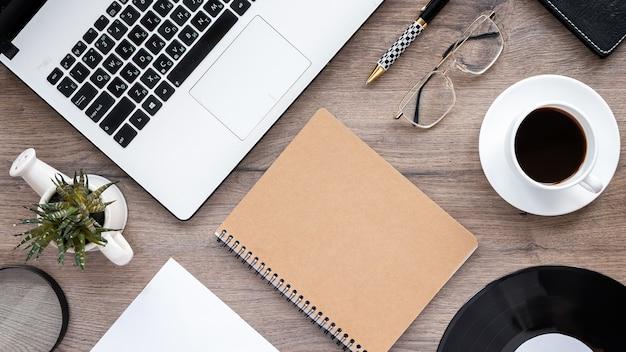 Tisch mit lifestyle-dingen. laptop, notizblock, tasse kaffee, gläser, lupe mit dekoration auf dem holztisch. draufsicht