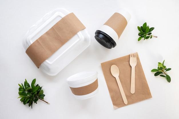 Tisch mit mittagessen sachen. lunchbox, eine tasse, geschirr und viel grün. draufsicht