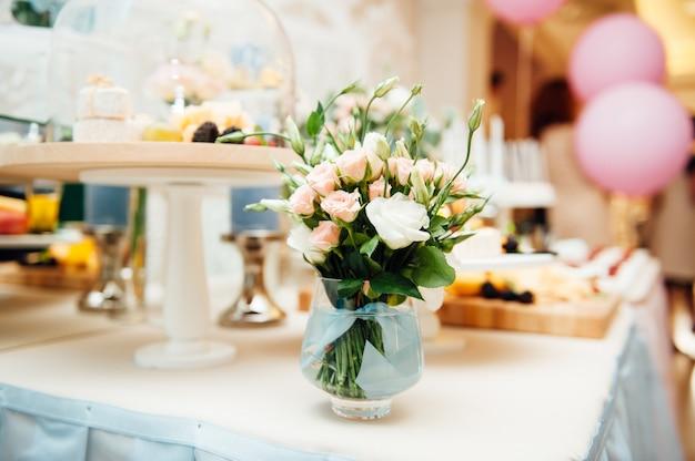 Tisch mit rosenstrauß gedeckt