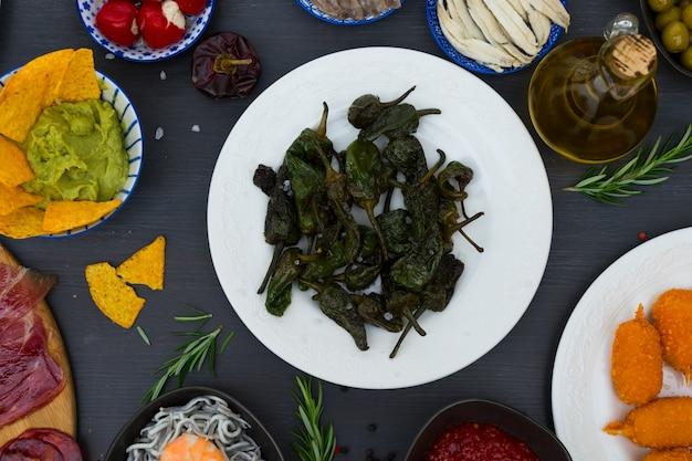 Tisch mit spanischen tapas - grüne padron-paprika, jamon, kroketten, guacamole und oliven