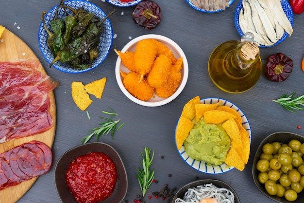Tisch mit spanischen tapas - grüne paprika padron, jamon, kroketten, guacamole und oliven, ansicht von oben