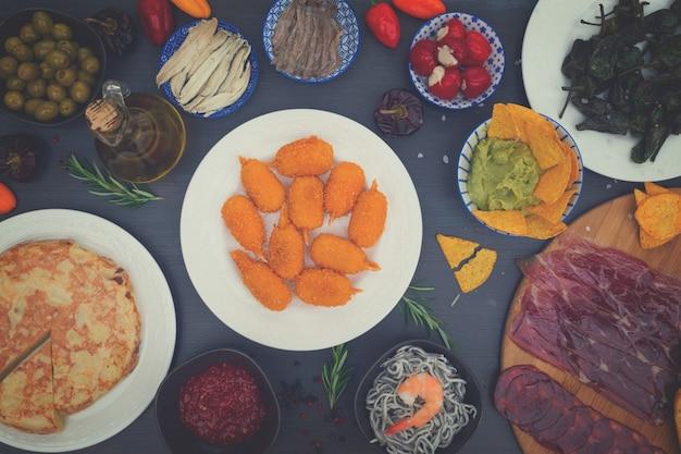 Tisch mit spanischen tapas - jamon, kroketten, guacamole und oliven, draufsicht, picknicktisch