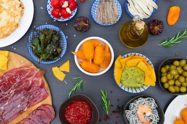 Tisch mit spanischen tapas - sardellen, grüner paprika padron, jamon, kroketten, guacamole und oliven
