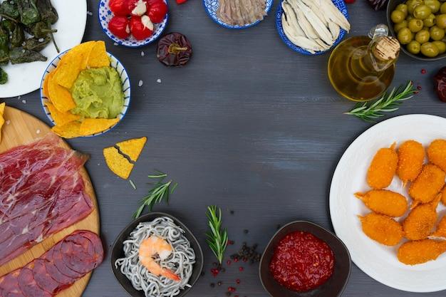 Tisch mit spanischen tapas - sardellen mit paprika padron, jamon, kroketten, guacamole und oliven