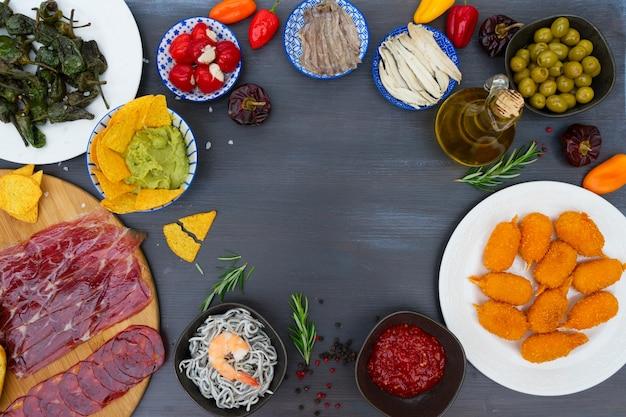 Tisch mit spanischen tapas - sardellen mit paprika padron, jamon, kroketten, guacamole