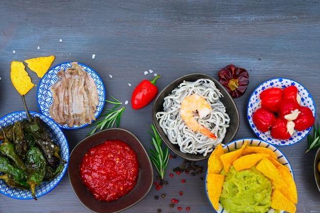 Tisch mit spanischen tapas - sardellen, paprika padron, jamon, cguacamole und oliven, draufsichtrand