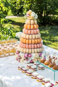 Tisch mit süßigkeiten mit blumen und makronenkuchen verziert