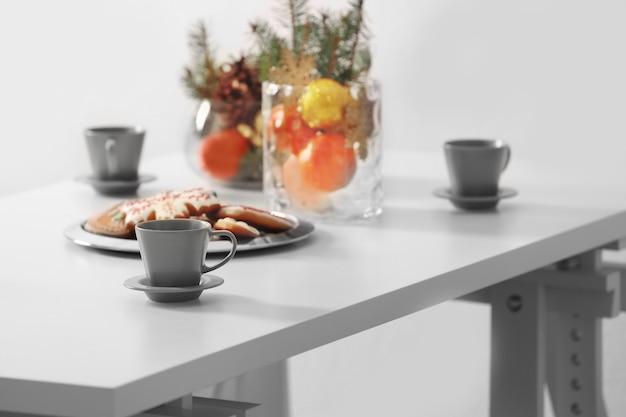 Tisch mit tassen und leckeren weihnachtsplätzchen, nahaufnahme