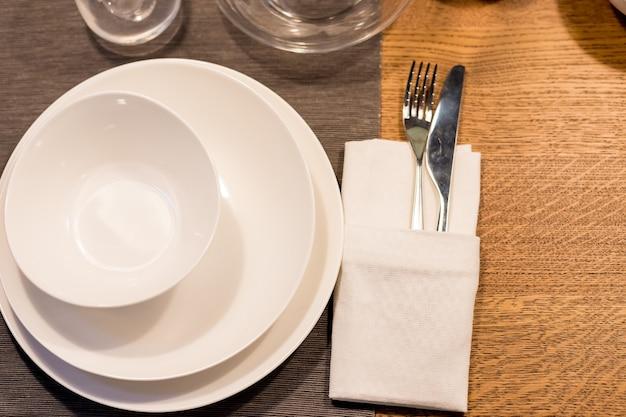 Tisch mit tellern und gläsern vor einer party. stapel von weißem keramikgeschirr, teller, untertassen, tassen auf einem holztisch. küchengeschirr. festlicher tisch