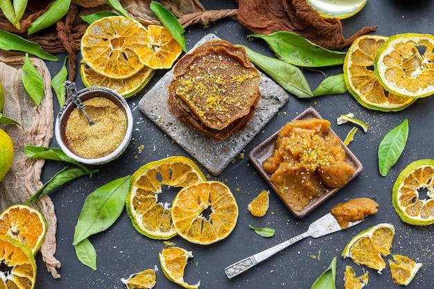 Tisch mit trockenen zitrusfrüchten und rohen pfannkuchen in der nähe einer schüssel voller mandarinenmarmelade