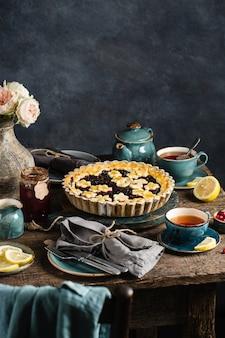 Tisch mit warmem beerentorte, heißen tassen mit zitronentee, marmelade und blumen