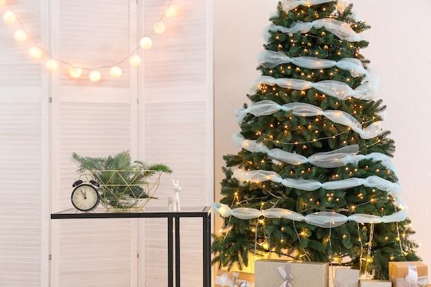 Tisch mit weihnachtsschmuck und schönem tannenbaum im innenraum des wohnzimmers