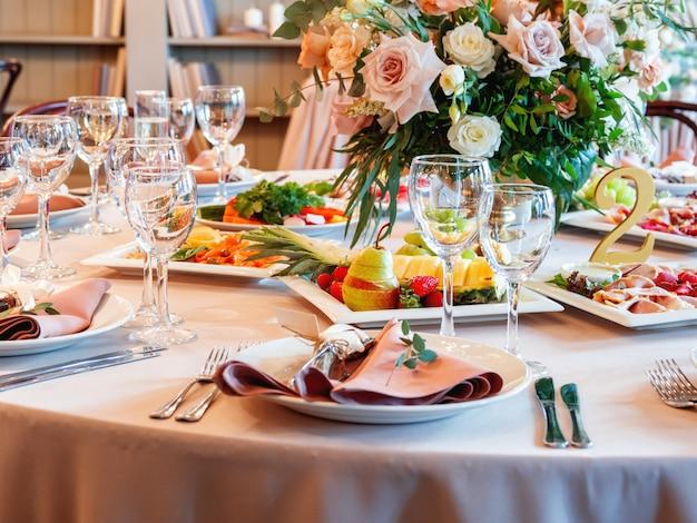 Tisch serviert für hochzeitsbankett mit besteck und blumen in vasen.