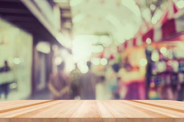 Tisch, theke im laden, hintergrund für produktpräsentationsvorlage, leerer holzschreibtisch, regal, theke über unscharfem einzelhandelsgeschäft mit abstraktem bokeh-lichthintergrund, holztischplatte und unschärfe-ladenhintergrund.